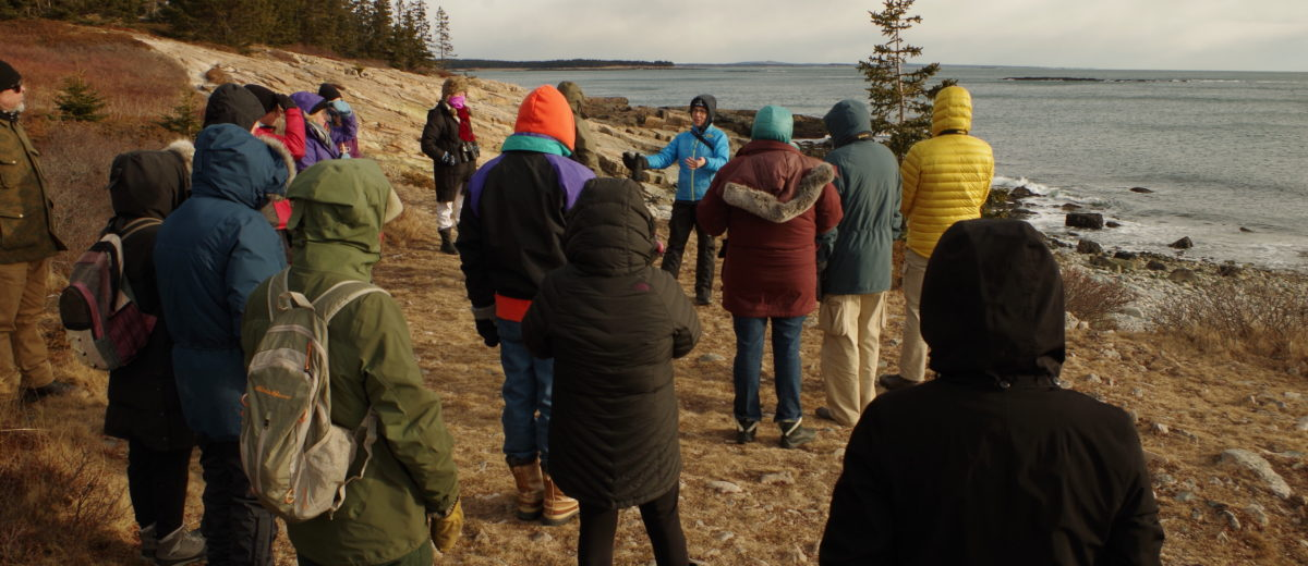 photo of people listening to one person on maine coast in winter