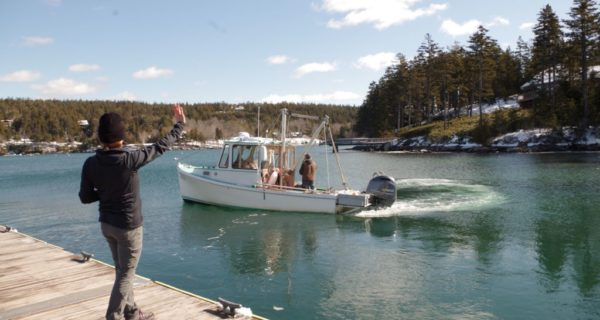 photo of person waving to people on lobster boat