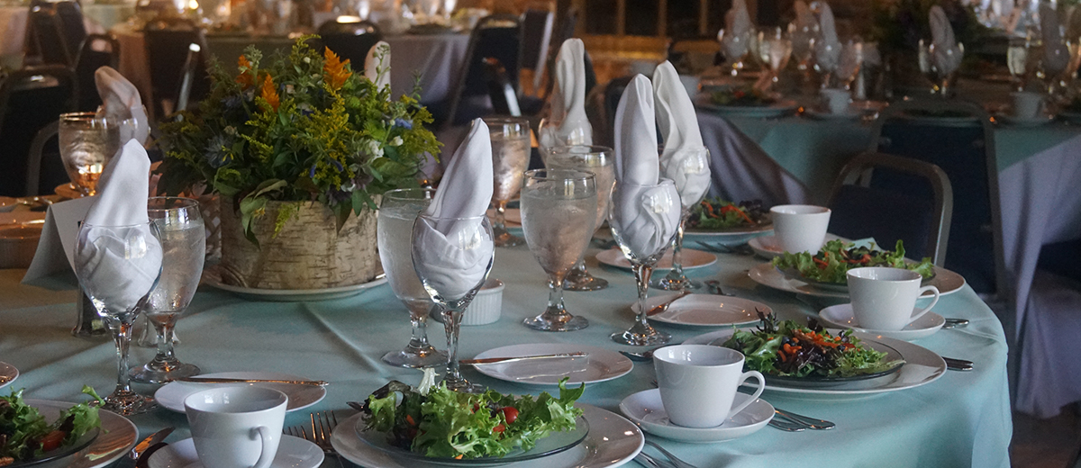 photo of set dining table with salads at each seat