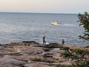 photo of two people walking along maine's rocky coast with lobster boat in background