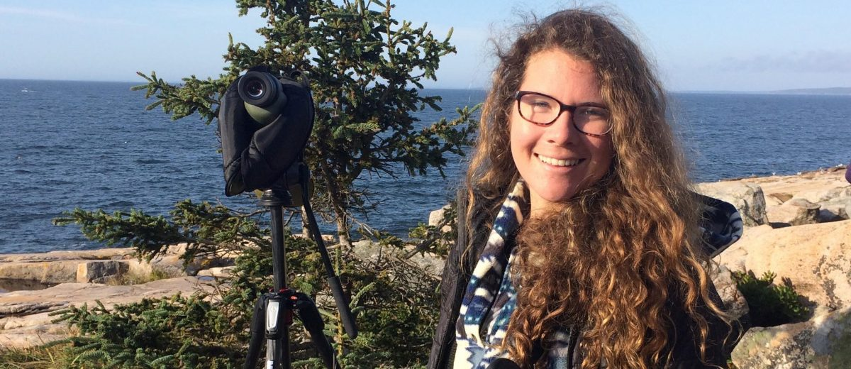 Hallie Daly stands next to spotting scope with tree and ocean i background