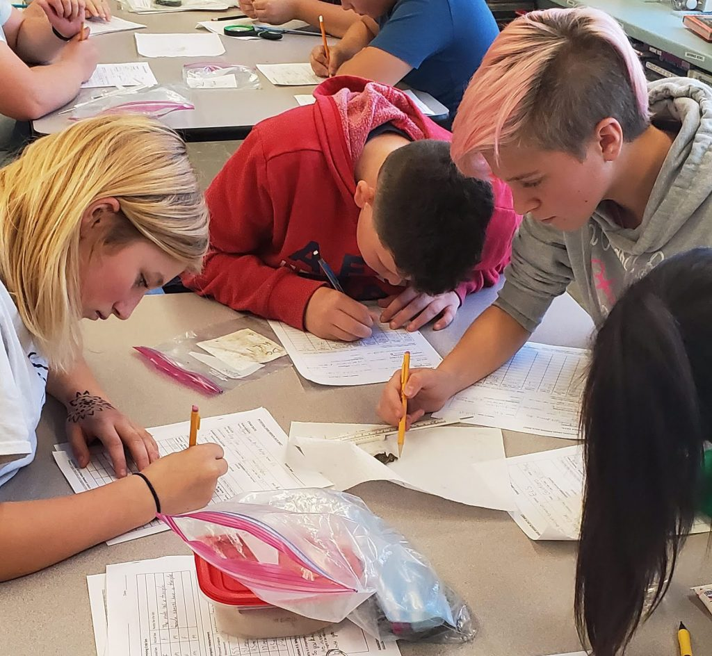 three students filling out worksheets