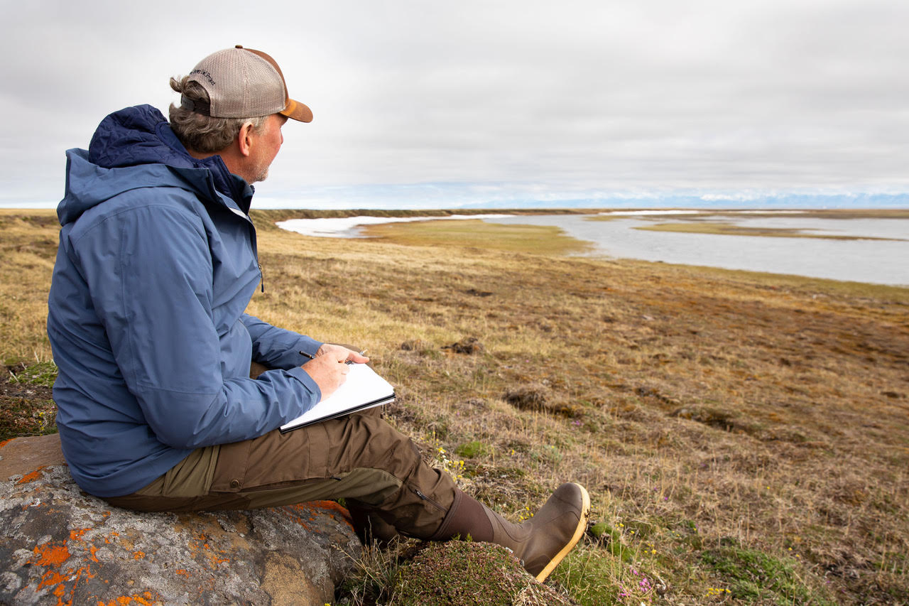 Michael Boardman sits on a rock looking out over brown Arctic marshes