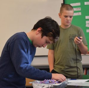 a student sifts through colored materials in a foil pan while another watches a timer