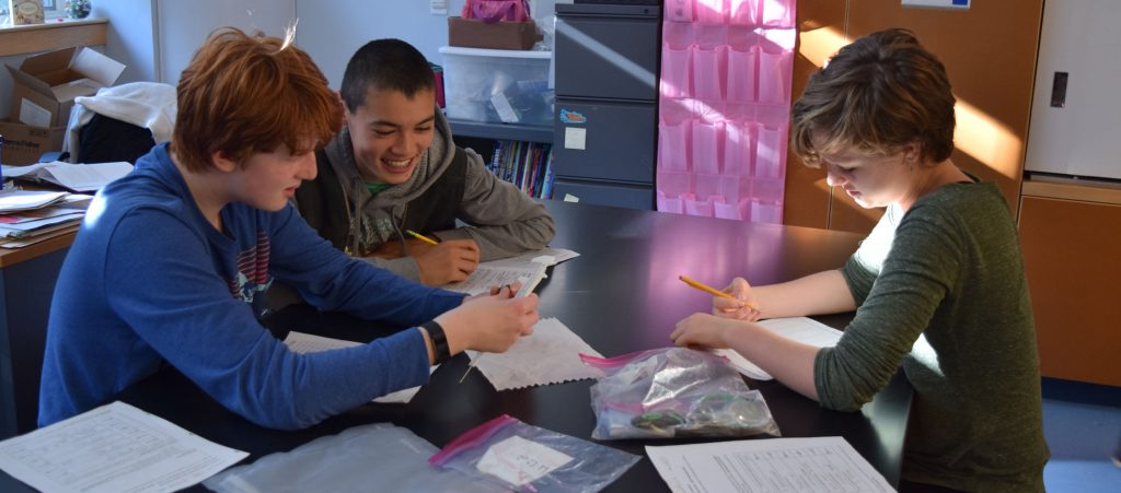 three students examine materials on a table