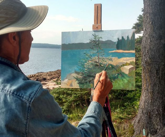 An artist paints at an easel outside on the coast.