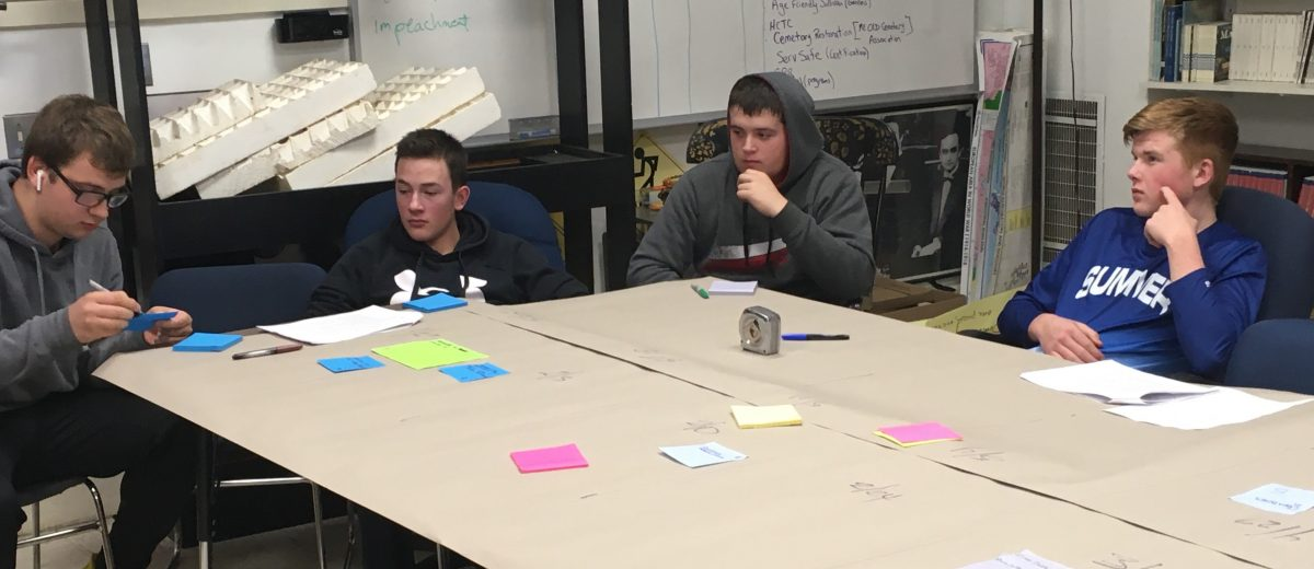 four students sit around a table