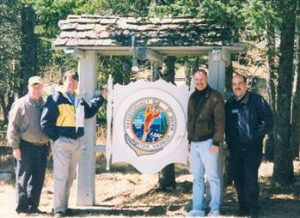 Personnel around front gate sign April 2002