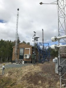 The monitoring station consists of metal towers and a small shed with various instruments on and around it.