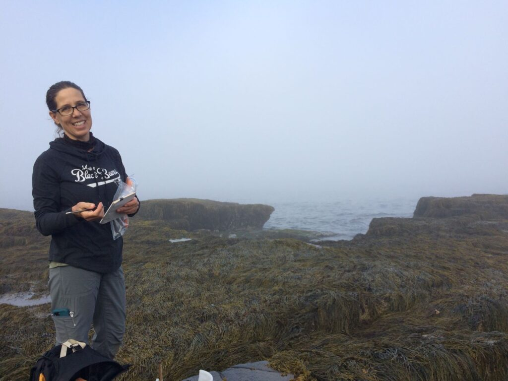 Hannah Webber smiling from the rockweed-covered rocks in the  low-tide zone