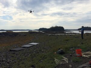 Stefan flies a drone over rockweed-covered shore. Calibration panels, square frames, and other gear in forefround.