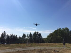 A pilot flies a drone from a gravel driveway with trees in background