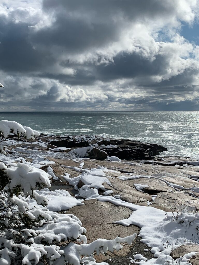 dramatic clouds and sun over the ocean and snow-covered rocks of schoodic point