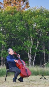 Yo-Yo Ma seated in a chair plays cello with grass, birch and spruce trees in background.