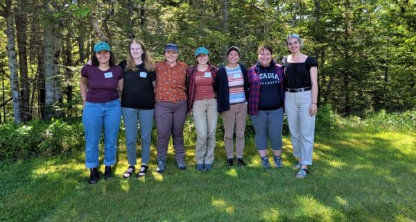 Seven of the nine Schoodic Institute techs and interns stand in a line with trees behind them