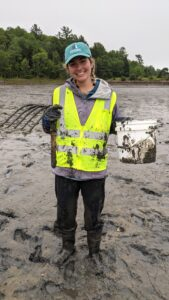 A muddy Elizabeth Halasz stands in the mudflat with clam rake and bucket.