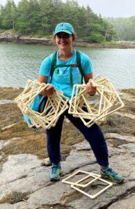 Jess Moskowitz stands on rocks in the intertidal zone holding sampling quadrats with water and trees in background.