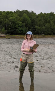 Anna Lee holds a clipboard and stands in shallow water with mud and trees in background.
