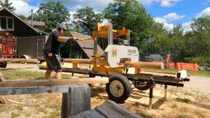 Mark Cross puts logs through a mechanical saw mill.