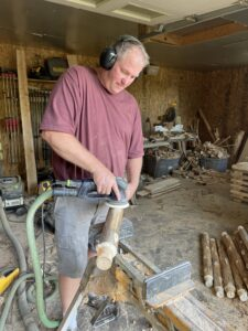 Mark Cross in his workshop sanding legs of what will become the benches.